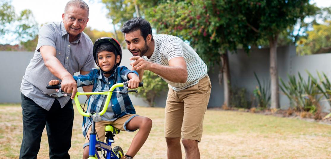 Grandfather, son, with grandson learning to ride bike