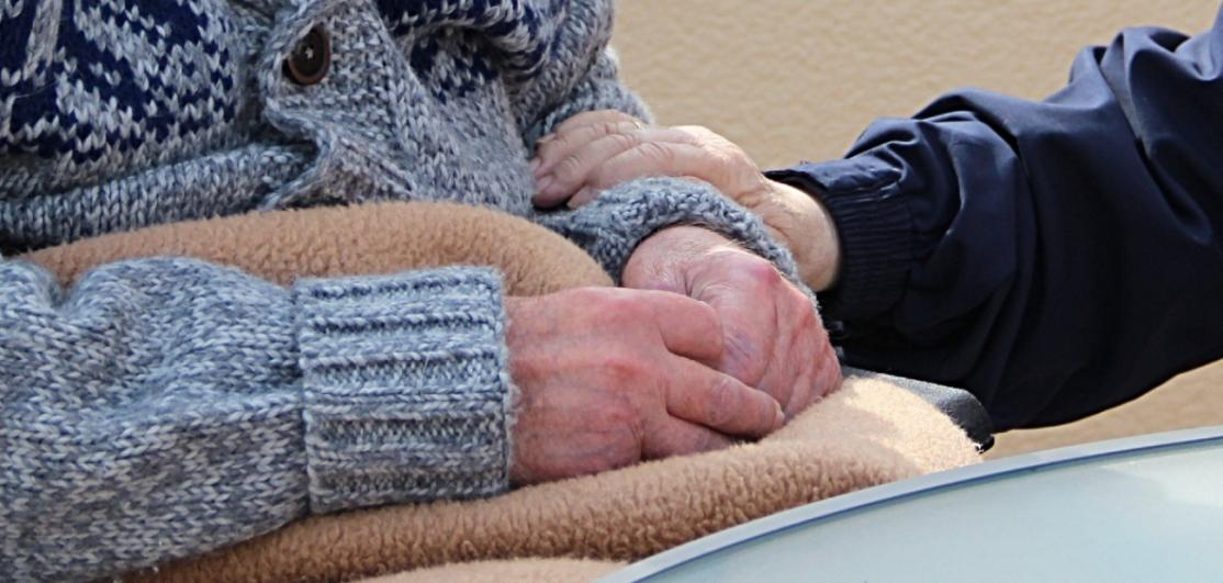 Senior sitting hands clasped over blanket, with another placing their hand on senior's arm