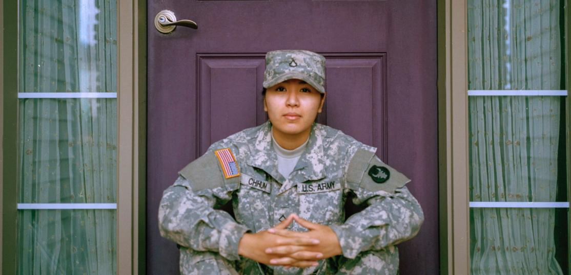 A woman in military garb sitting on the front steps of her home