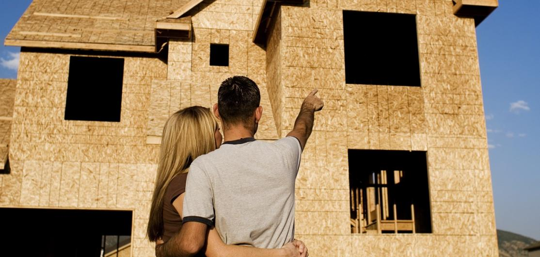 Couple in front of new home under construction.