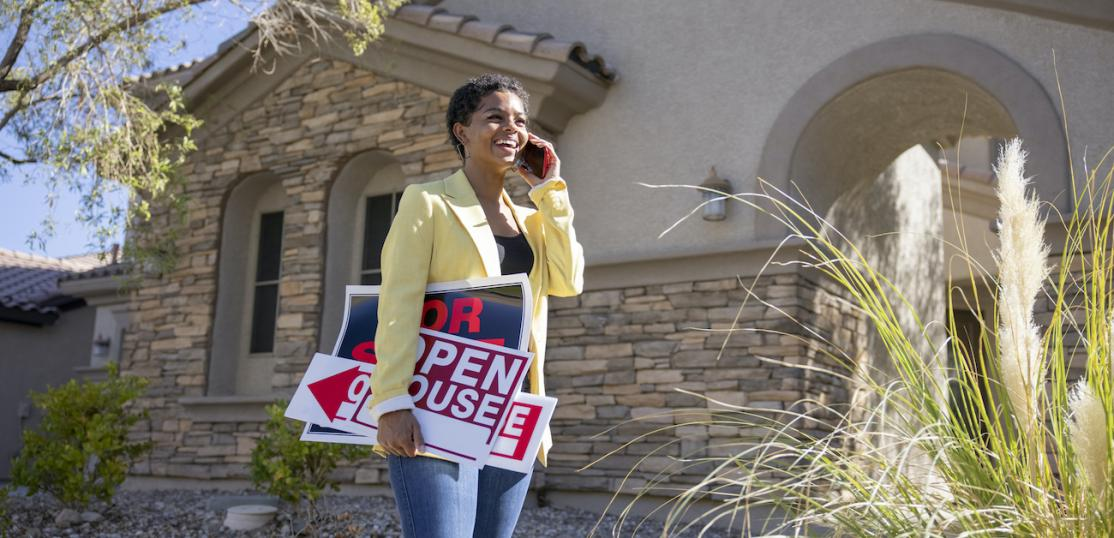 Real estate agent outside home with open house sign