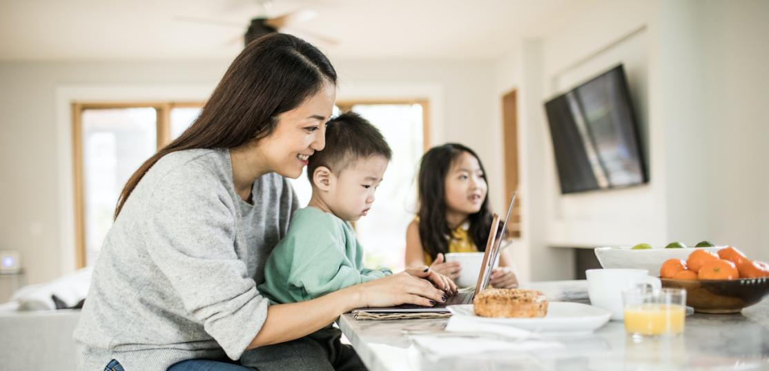 Mother multi-tasking with young children in kitchen table.