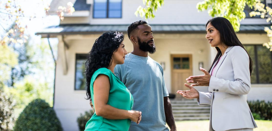 Real estate agents speaking with couple outside a house.