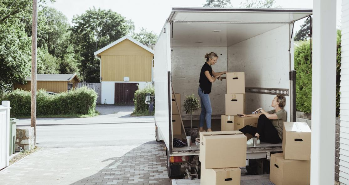 Two women loading boxes into moving truck.