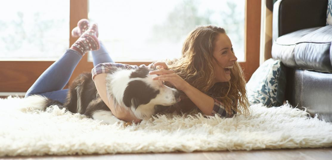 Woman with her dog on a rug