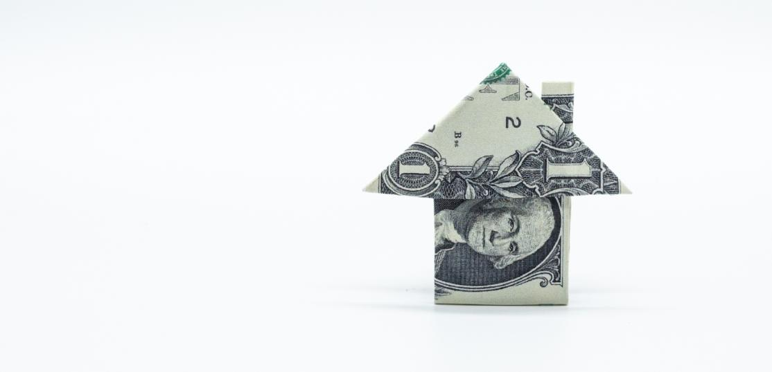 A dollar bill folded into a depiction of a house