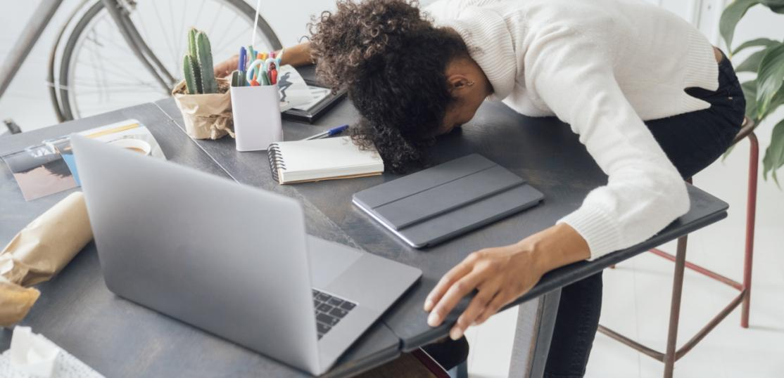 A woman face down sleeping at her desk