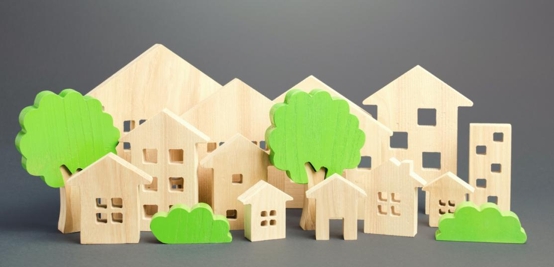 Different size model houses and green trees representing a city