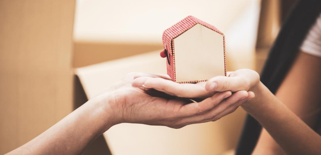 Clasped hands holding a small model house