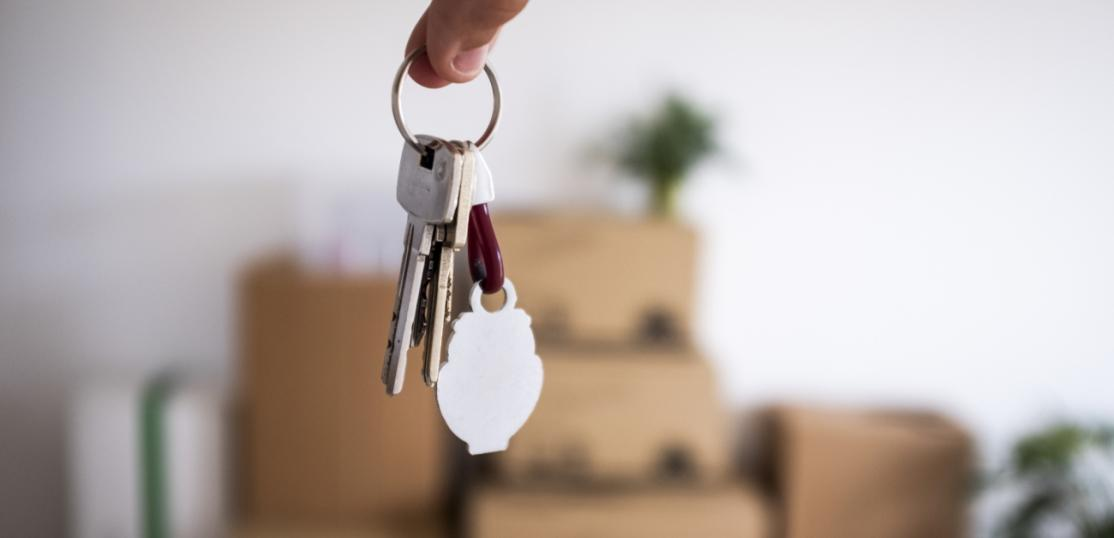 Boxes against a wall, person holding keys