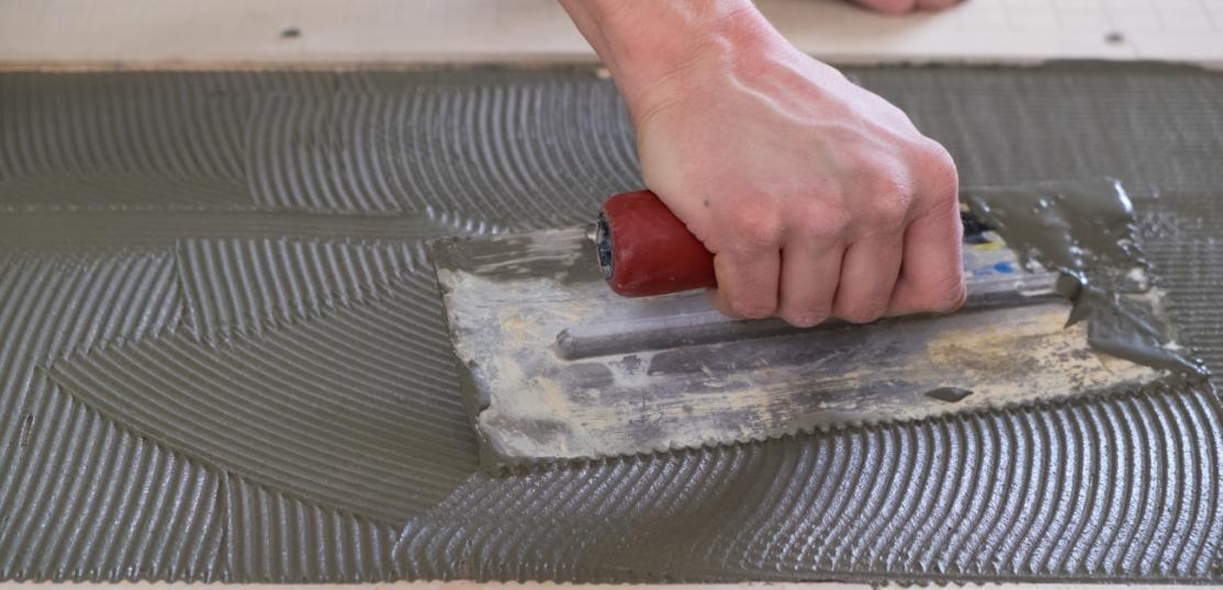 Person laying cement on a floor
