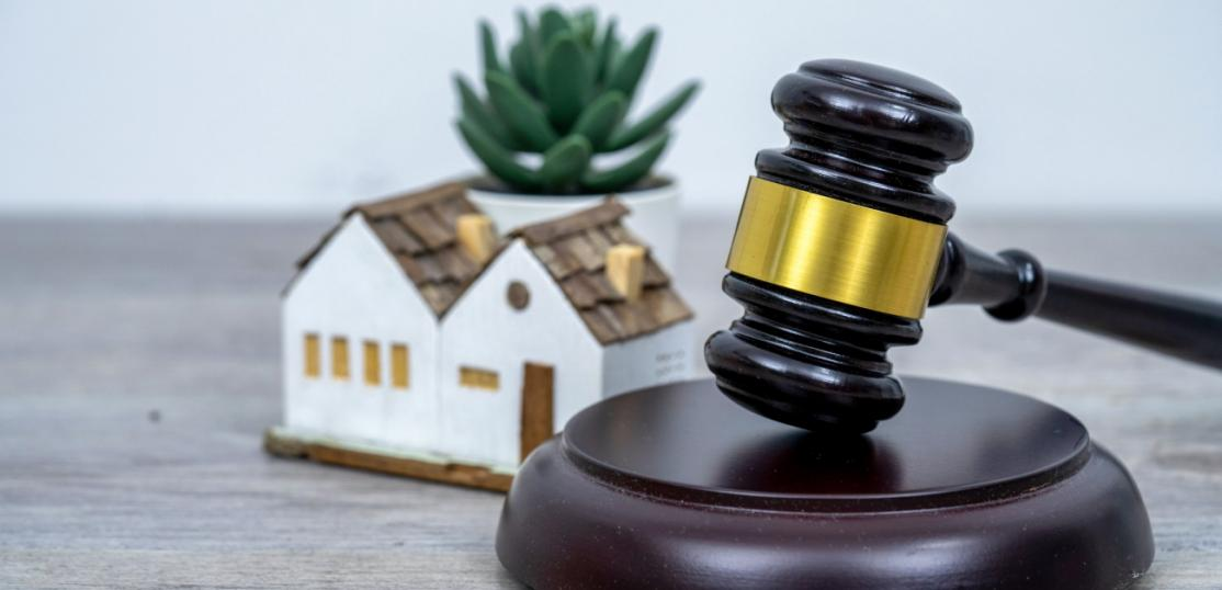 An auction gavel sits to the center right in the frame, with a small house miniature slightly behind it.