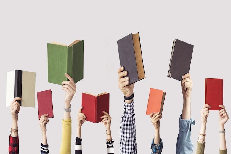 a group of hands holding up books
