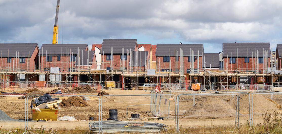 row of new homes being constructed with crane in background