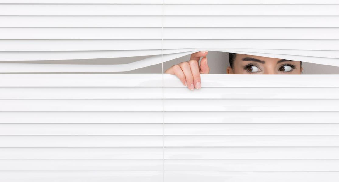 Woman looking through blinds with suspicion or fear