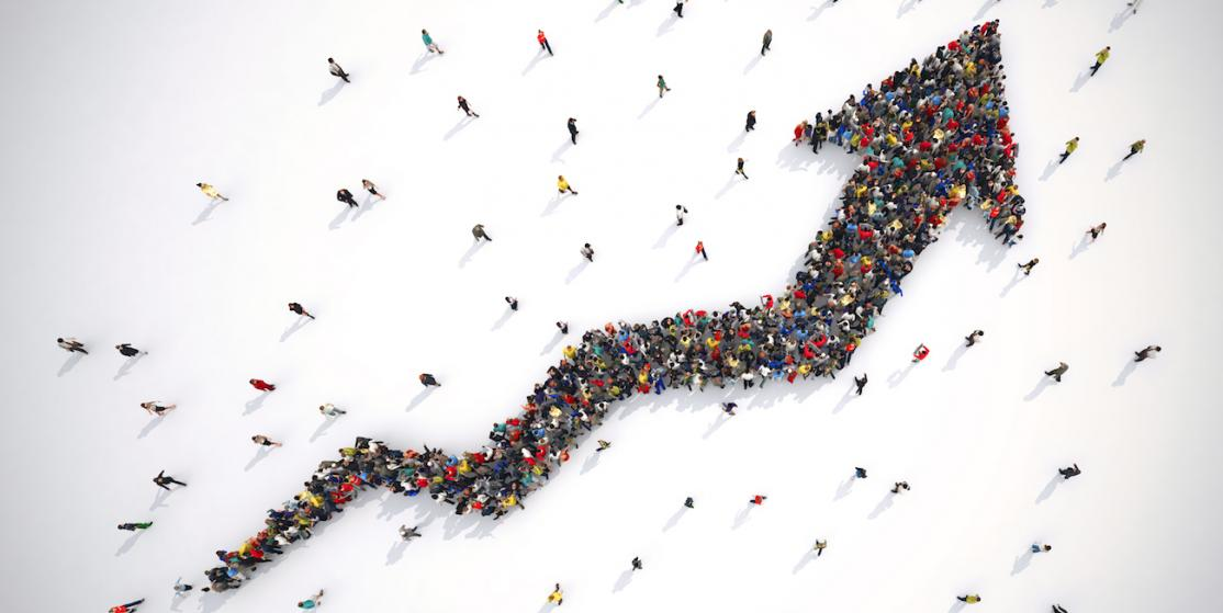 Birds-eye view of a group of people coming together to form an upward facing arrow