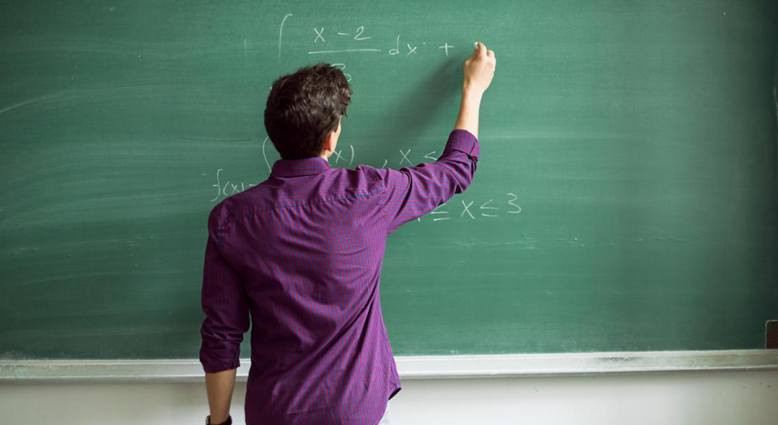 Person in front of blackboard working on math problem