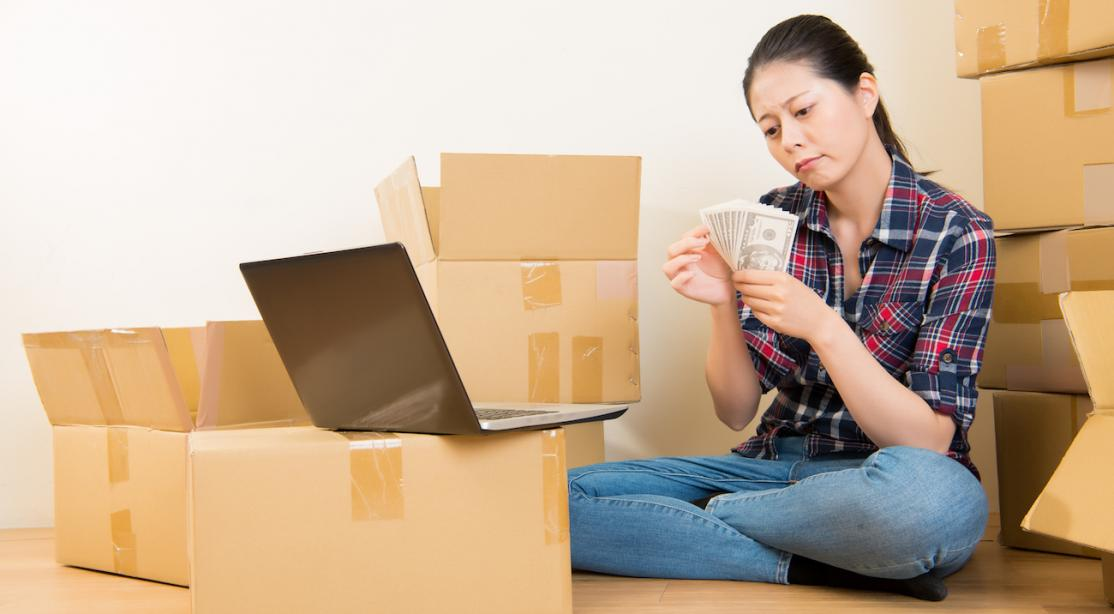 Woman sitting on hardwood floor in front of laptop on moving boxes, counting cash