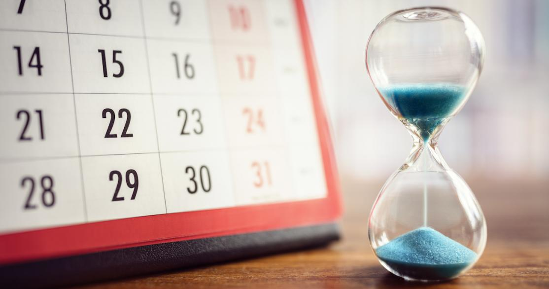 Hourglass with blue sand running out in front of a calendar