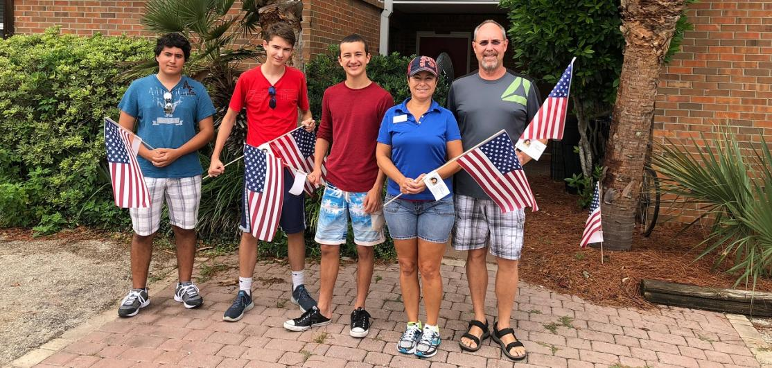 Silvia Madriaga and her family hold American flags