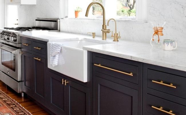 a photo of a kitchen with navy cabinets and brass details