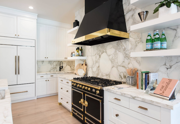 A kitchen with black stove and black exhaust hood with brass fittings and trim
