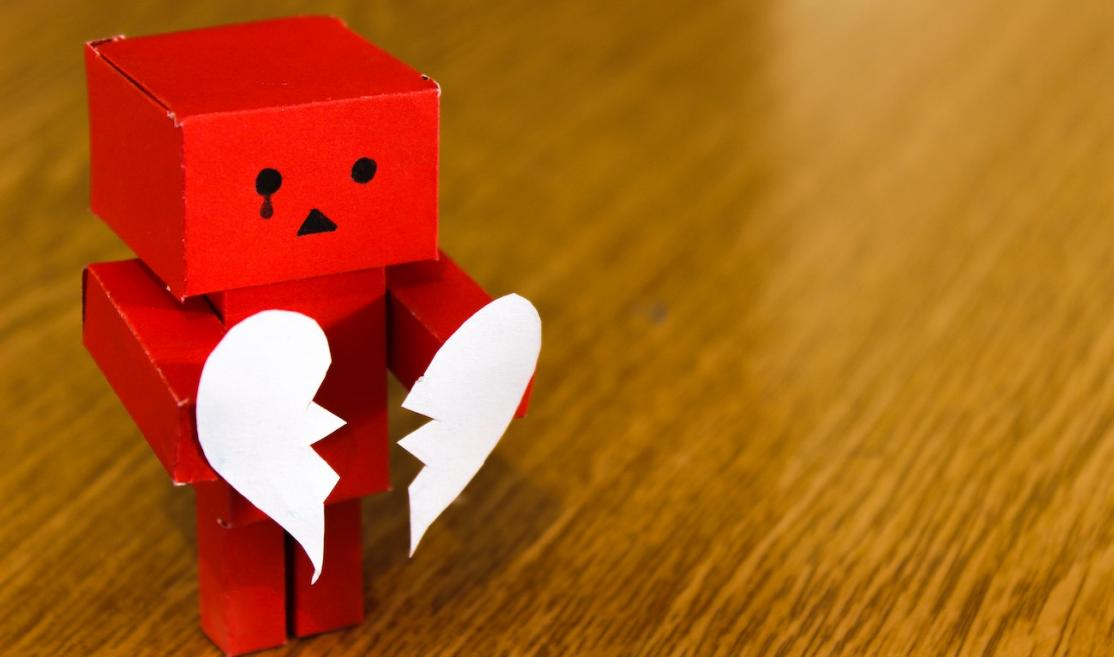 Red paper robot crying and holding white broken heart