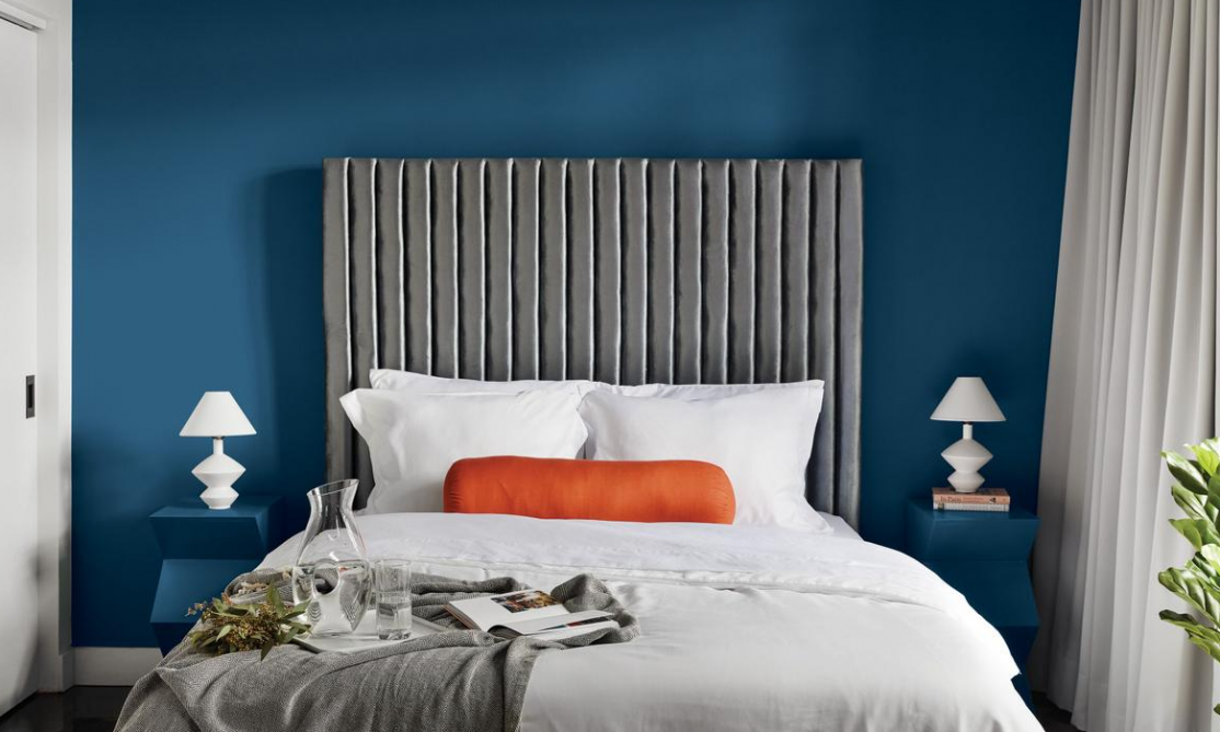 a bedroom with a dark blue wall