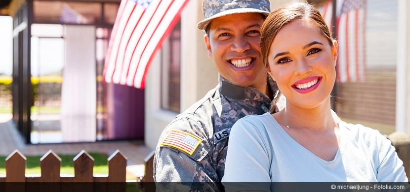 Veteran and spouse smile, embrace in front of home