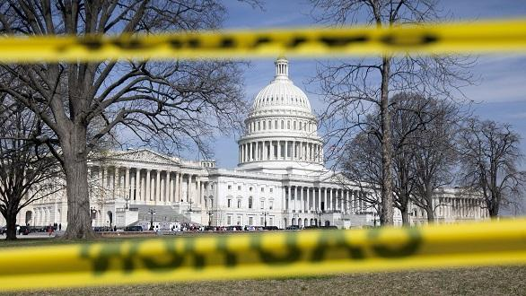 "The U.S. Capitol building seen through yellow ""caution"" tape"