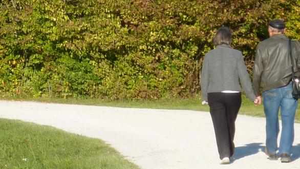 An older couple walking hand in hand