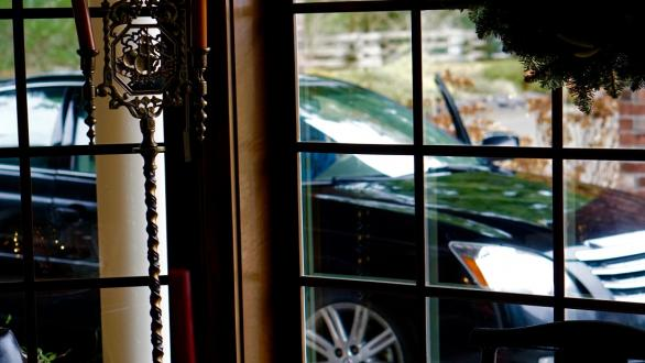 An expensive car viewed from the inside of an ornate home.