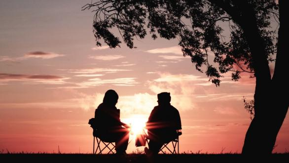 A retired couple in chairs in a park watching the sun set