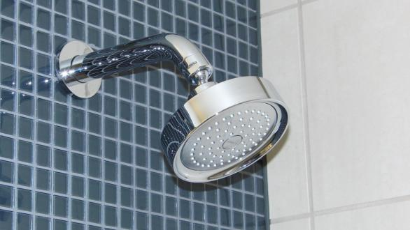 A showerhead installed in a tile wall.