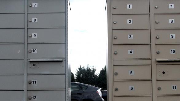 Many locked mailboxes outside in a parking lot