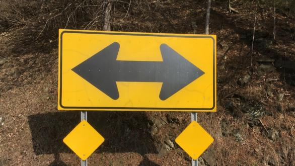 A road sign with arrows pointing in opposite directions.