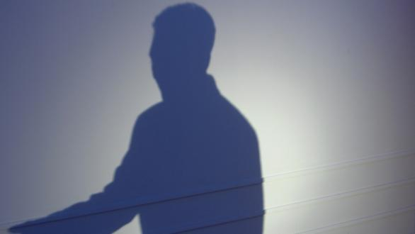 The shadow of a person standing at a podium