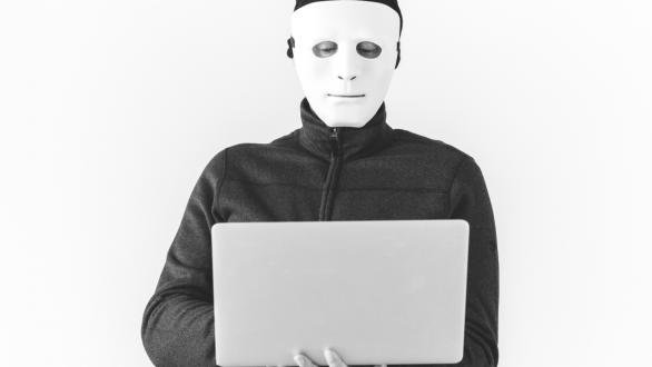 A masked man working at a laptop computer
