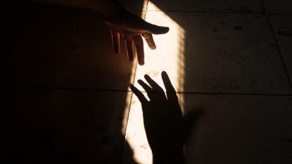 Two shadowed hands reaching out to each other