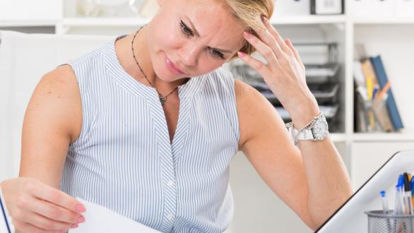 stressed woman looking at bills