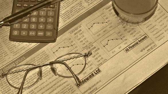 Glasses and a calculator on a newspaper's financial news page