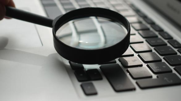 A magnifying glass over a computer keyboard