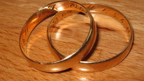 Two wedding rings on a wooden table