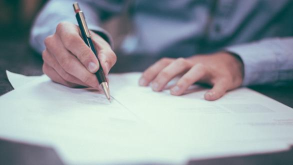 A man signing documents at a table