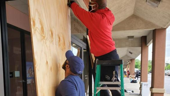 crew boards up storefront windows