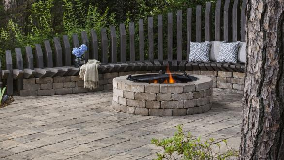 stone backyard fire pit with seating area
