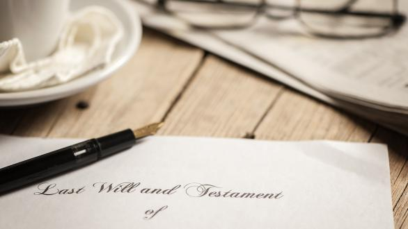 Table with last will and testament, pen, coffee cup, glasses, and newspaper