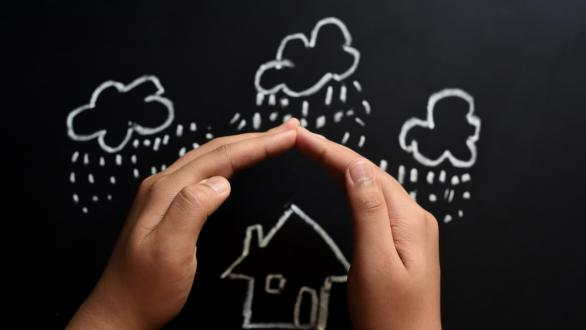 Two hands sheltering image of house drawn in chalk from rain