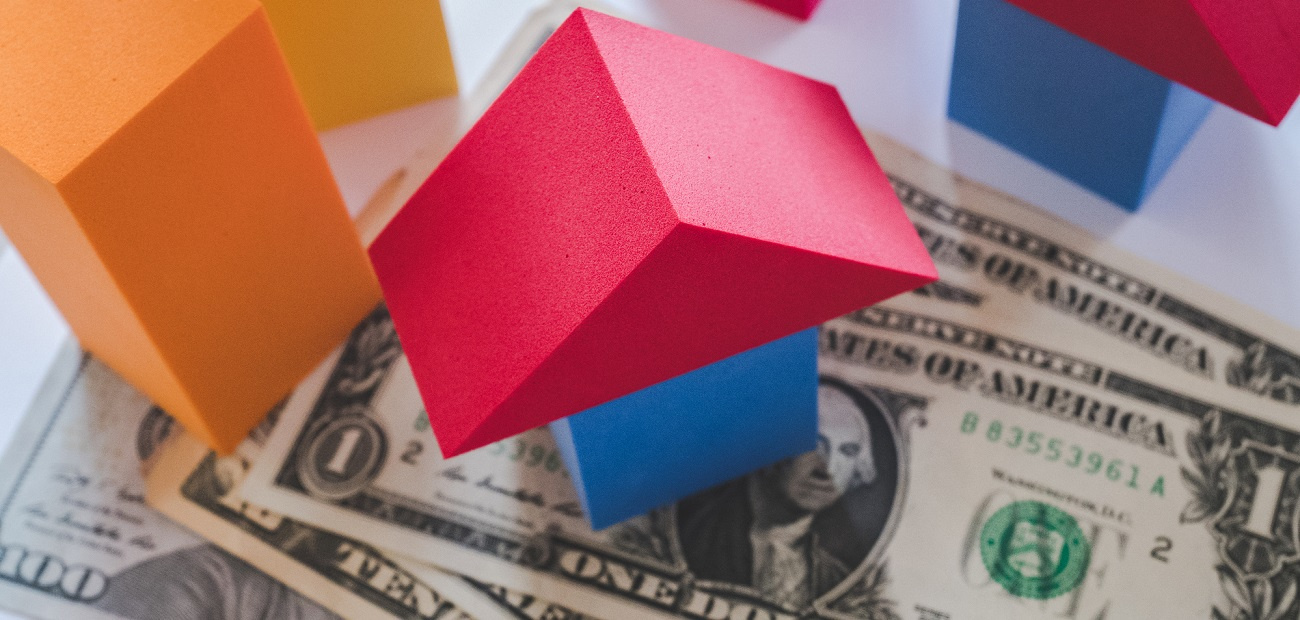 Blocks forming a house, sitting on top of cash