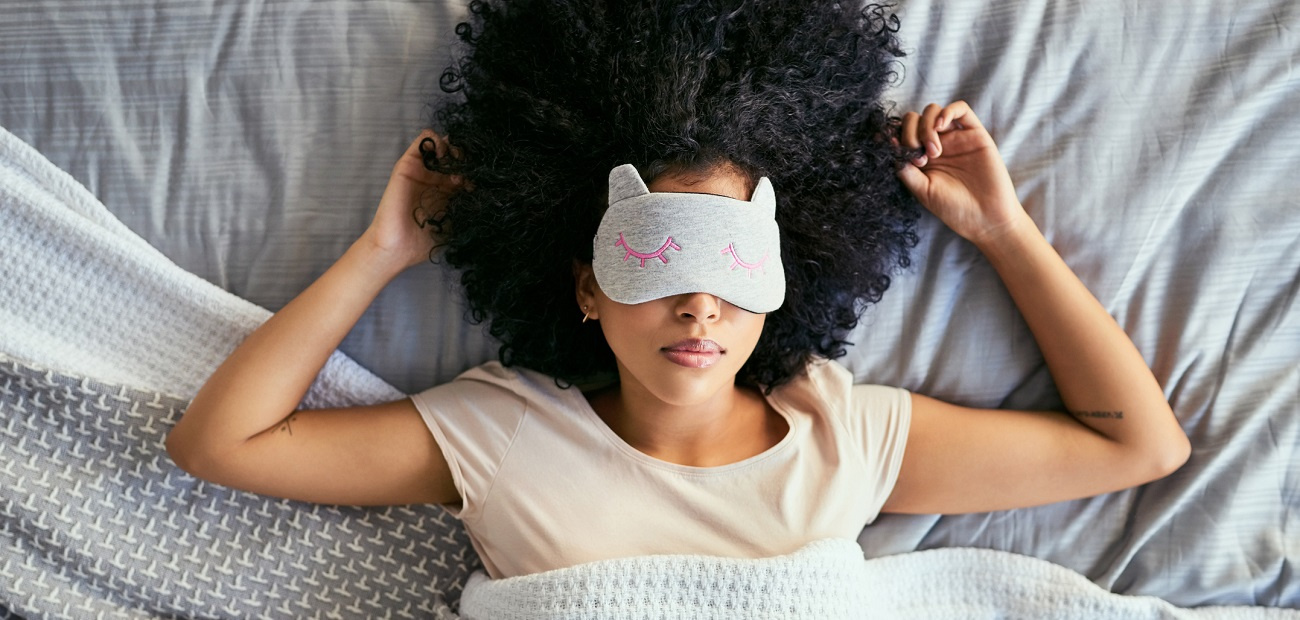 young woman sleeping with a mask on in bed